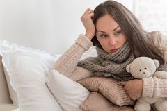 Sad thoughtful woman lying on pillows Royalty Free Stock Images