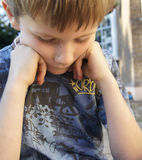 Sad thoughtful worried young boy. A simple portrait of a little boy who is deep in thought, worried, concerned, thinking, unhappy, anxious.  Taken outdoors in Stock Images