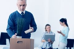 Sad mature man packing his stuff in box at work Stock Images