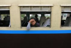A sad and tired Burmese girl looking out of the window of an old train royalty free stock photos