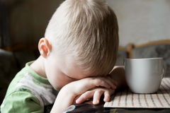 Sad tired child. Sad upset tired worried little child (boy) lying on his hands close up portrait Royalty Free Stock Image