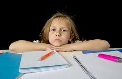 Sad tired cute blond junior schoolgirl in stress working doing homework bored overwhelmed Stock Photo