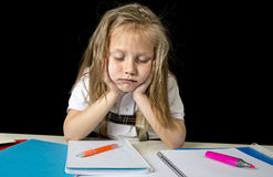 Sad tired cute blond junior schoolgirl in stress working doing homework bored overwhelmed. Sad and tired cute junior schoolgirl with blond hair sitting in stress Royalty Free Stock Image