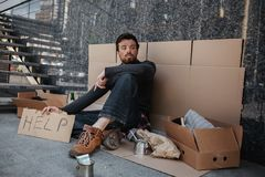Sad and tired dark-haired man is sitting on the cardboard and holding another cardboard with the word help writing on it stock image