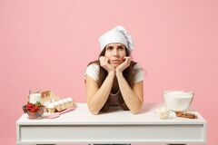 Sad tired female chef cook confectioner or baker in apron white t-shirt, toque chefs hat cooking cake or cupcake at