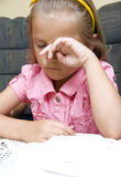 Sad or tired girl. A sad or tired little girl sitting at a table, rubbing her eyes royalty free stock photography