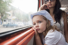 Sad and tired girl looks through the window in the tram Stock Image