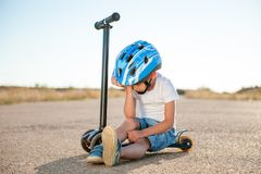 Sad tired injured little boy in blue sport helmet sitting on scooter on road royalty free stock photo