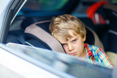 Sad tired kid boy sitting in car  during traffic jam. Sad little kid boy sitting in car in traffic jam during going for summer vacation with his parents. Tired Royalty Free Stock Image