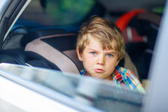 Sad tired kid boy sitting in car  during traffic jam Stock Photos