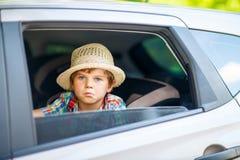 Sad tired kid boy sitting in car  during traffic jam Stock Image