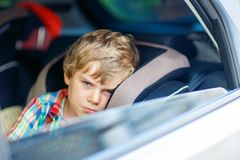 Sad tired kid boy sitting in car  during traffic jam Royalty Free Stock Photo