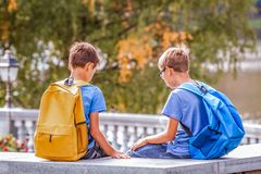 Sad tired kids after school, sitting on bench outdoors.  royalty free stock photography