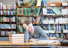 Sad and tired male student n library Royalty Free Stock Photo