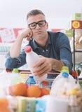 Sad man doing grocery shopping stock image
