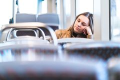 Sad tired woman in train or bus. Bored or unhappy passenger stock image