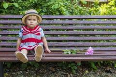 Sad toddler sitting on a bench Royalty Free Stock Photos