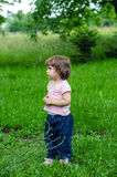 Sad Toddler Standing in Grass Royalty Free Stock Image