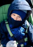 Sad toddler in a stroller on cold winter day Stock Image
