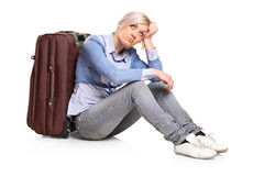 Sad tourist girl seated next to a suitcase Royalty Free Stock Photography