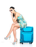 Sad tourist woman seated next to a suitcase Stock Photo