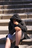 Sad troubled teenager school boy with hood on posing outdoor sitting alone on the street wearing a hoodie and dark sunglasses posi stock photography