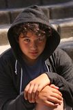 Sad troubled teenager school boy with hood on posing outdoor sitting alone on the street royalty free stock photography
