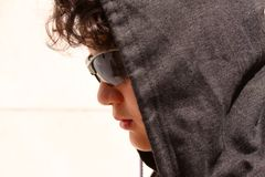 Sad troubled teenager school boy with hood on posing outdoor sitting alone on the street wearing a hoodie and dark sunglasses posi royalty free stock photography