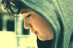 Sad troubled school boy teenager wearing a hood - close up in instant photo style with subdued colors stock images