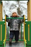 Sad two year old girl hesitating and unwilling to slide on the winter playground. Disappointed facial expression Royalty Free Stock Image