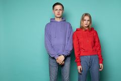 Sad unhappy couple, beautiful blonde girl in red hoodie and handsome boy in purple hoodie royalty free stock image
