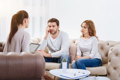Sad unhappy couple listening to the psychologist. Psychological advice. Sad unhappy young couple looking at the psychologist and listening to her while sitting royalty free stock images