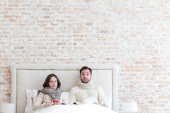 Sad unhappy couple lying in bed together. Being ill. Cheerless unhappy young couple lying together on a bed and looking in front of them while having cold Stock Images