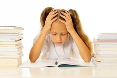 Sad unhappy cute little girl overwhelm with homework and studies. Sad and tired cute schoolgirl with blond hair sitting in stress doing homework overwhelm with stock photography