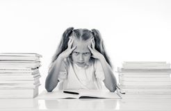 Sad unhappy cute little girl overwhelm with homework and studies. Sad and tired cute schoolgirl with blond hair sitting in stress doing homework overwhelm with royalty free stock photos