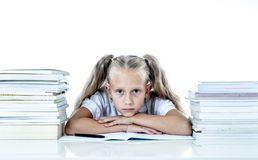 Sad unhappy cute little girl overwhelm with homework and studies. Sad and tired cute schoolgirl with blond hair sitting in stress doing homework overwhelm with stock image
