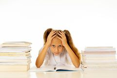 Sad unhappy cute little girl overwhelm with homework and studies. Sad and tired cute schoolgirl with blond hair sitting in stress doing homework overwhelm with stock photo