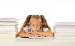 Sad unhappy cute little girl overwhelm with homework and studies. Sad and tired cute schoolgirl with blond hair sitting in stress doing homework overwhelm with royalty free stock photo