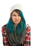 Sad and unhappy girl looking straight at camera. Pierced, turquoise haired and dressing up a plaid jacket and white cap Royalty Free Stock Photos