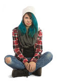 Sad and unhappy girl sitting cross-legged. And looking straight at camera. Pierced, turquoise haired and dressing up a plaid jacket and blue jeans Royalty Free Stock Photo