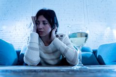 Sad, unhappy, helpless woman drinking wine alone at home. Human emotions, depression and alcoholism. Stressed and hopeless young woman drinking a glass of wine royalty free stock photo