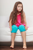 Sad unhappy little girl kid sitting on sofa. stock photos
