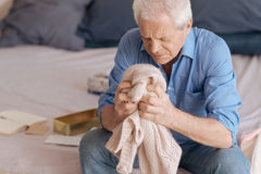 Sad unhappy man holding his wifes knitted jacked. Painful memories. Sad unhappy senior man sitting in the bedroom and holding his wifes knitted jacked while Stock Photography