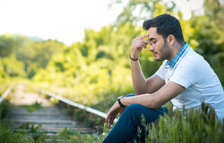 Sad or unhappy man sitting on a train lines. Outdoor, outside Royalty Free Stock Photo