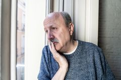 Sad unhappy old senior man suffering from memory loss and alzheimer feeling depressed and lonely royalty free stock image