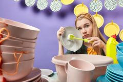 Sad unhappy serious young woman using brush while doing household chores stock photography
