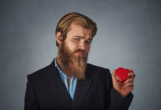 Upset man standing and holding red big heart shape royalty free stock photos