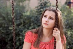 Sad unhappy teen girl with long brunette hair sitting on a swing sadly looking up royalty free stock image