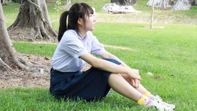 Sad Unhappy thai student teen Sitting On Park stock video footage