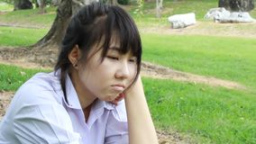 Sad Unhappy thai student teen Sitting On Park stock video